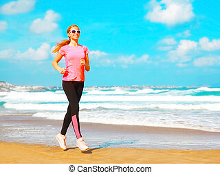 Fitness young woman is running along the beach near the sea on a summer day