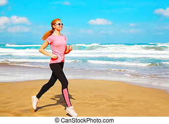 Fitness young woman is running along the beach near the sea
