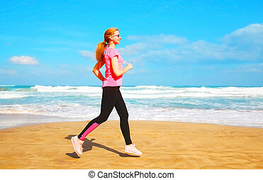 Fitness young woman is running summer along the beach near the sea at summer day