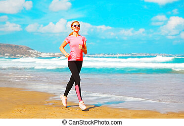 Fitness young woman is running summer along the beach near the sea