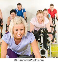 Fitness young woman on gym bike spinning