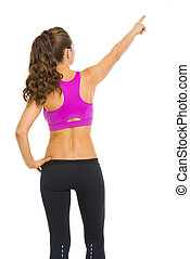 Fitness young woman pointing on copy space . rear view