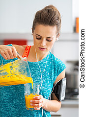 Fitness young woman pouring pumpkin smoothie in glass