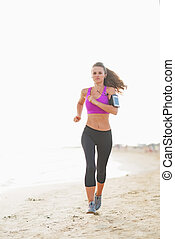 Fitness young woman running on the beach
