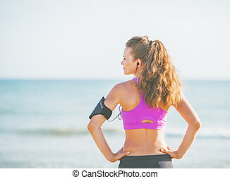 Fitness young woman standing on beach and looking on copy space. rear view