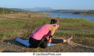 Fitness young woman stretching legs before exercise outdoors