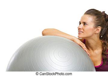 Fitness young woman with fitness ball looking on copy space