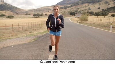Fitress Girl Running on the Road in Mountains