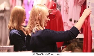 Fits best - Young blonde choosing clothes in a shopping mall...