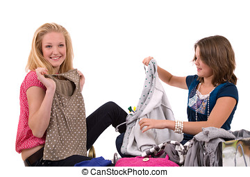 Fitting clothes - Two teenage girls going through a pile of...