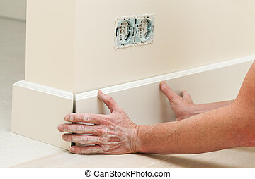 Fitting the baseboard - Hands fitting the baseboard to a...