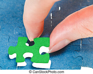 fitting the last green piece of puzzle