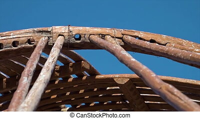 Fitting wooden poles into holes of framework - A close-up ...