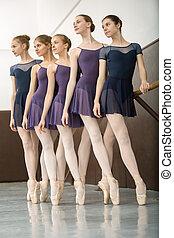 Five ballet dancers in class near the barre. Model wearing white tights. Girls look toward