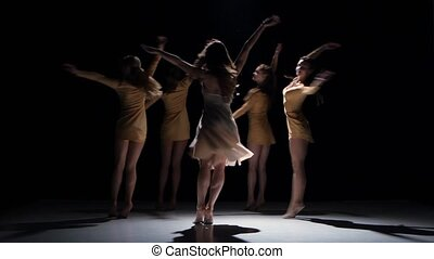 Five beautiful girls in white and bage dresses continue dancing modern contemporary dance, on black background, shadow