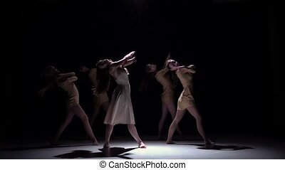 Five beautiful girls in white and bage dresses continue dancing modern contemporary dance, on black background, shadow, slow motion