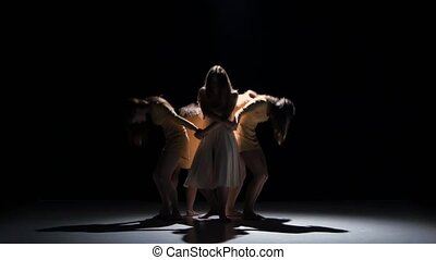 Five beautiful girls in white and bage dresses dancing modern contemporary dance, on black background, shadow