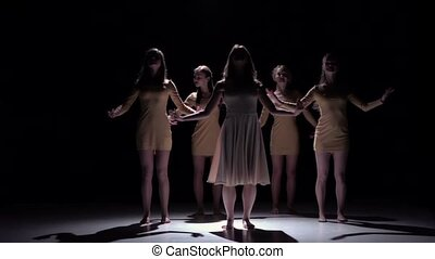 Five beautiful girls dancing modern contemporary dance, on black, shadow, slow motion