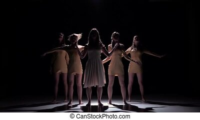 Five beautiful girls go on dancing modern contemporary dance, on black, shadow, slow motion