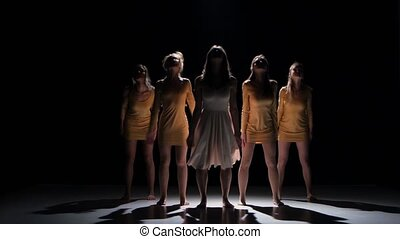 Five beautiful girls in white and bage dresses start dancing modern contemporary dance, on black background, shadow