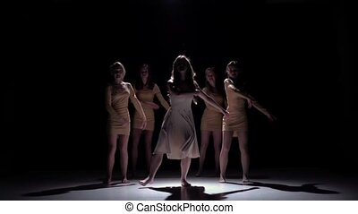 Five beautiful girls in white and bage dresses start dancing modern contemporary dance, on black background, shadow, slow motion