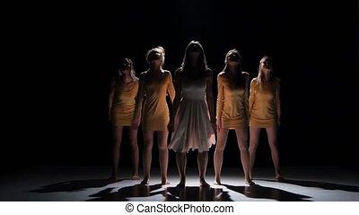 Five beautiful girls start dancing modern contemporary dance, on black, shadow
