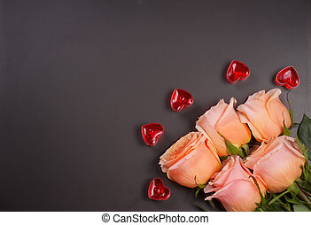 five beige rose with candles in the shape of heart on a dark...