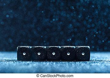 Five black identical dice lie side by side on a blue...