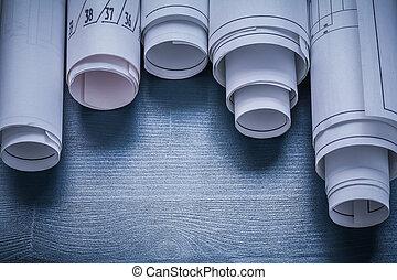 five blueprints rolled up on blue board