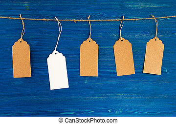 Five brown and white blank paper price tags or labels set hanging on a rope on the blue wooden background.