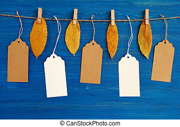 Five brown and white blank paper price tags or labels set hanging on a rope with dry yellow autumn leaves on the blue wooden background.