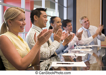 Five businesspeople at boardroom table applauding and...