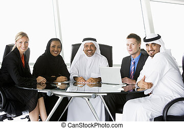 Five businesspeople in office with laptop smiling (high key/selective focus)
