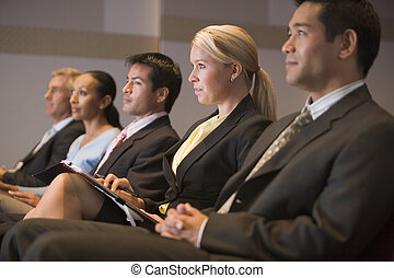 Five businesspeople sitting in presentation room with clipboards