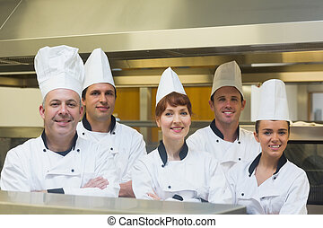Five chefs posing with crossed arms