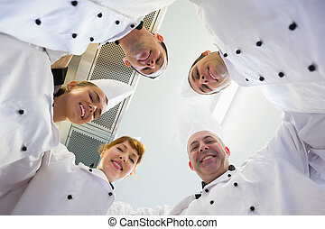 Five chefs standing in a circle wearing uniforms in a ...