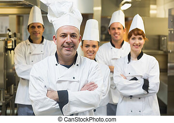 Five chefs wearing uniforms posing in a kitchen with crossed...