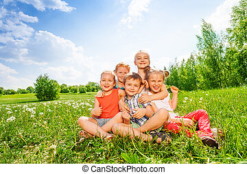 Five children sit together on a meadow