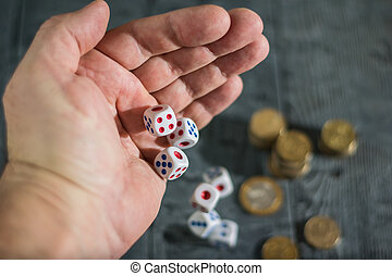 Five dice roll with left hand men on the table with money.