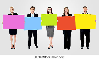 Five diverse professionals holding a blank banner