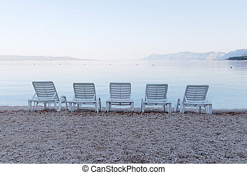 Five empty deck chair and distant mountains