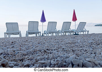 Five empty deck chair and parasol from a low angle