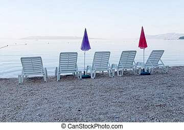 Five empty deck chair and parasol