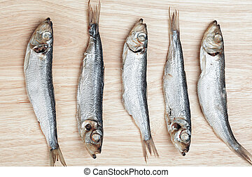 Five fishes on cutting board facing opposite direction