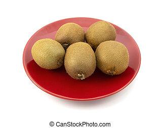 Five fresh whole kiwi fruits on a red plate
