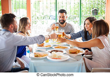 Five friends making toast at a barbecue