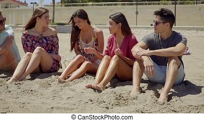 Five friends talking while sitting on sand