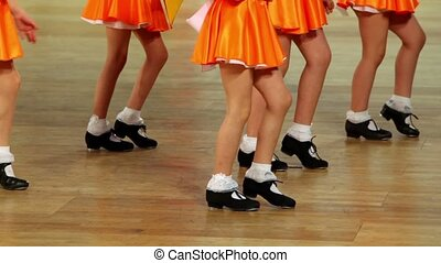 Five girls in shoes with taps and orange skirts tap dance, only legs are visible