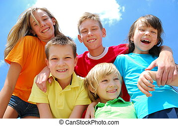 A view looking upwards at five, happy, smiling kids with blue sky and wispy white clouds in the background.