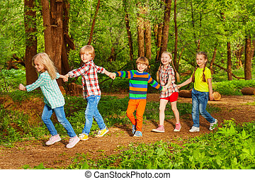 Five happy kids walking in forest holding hands